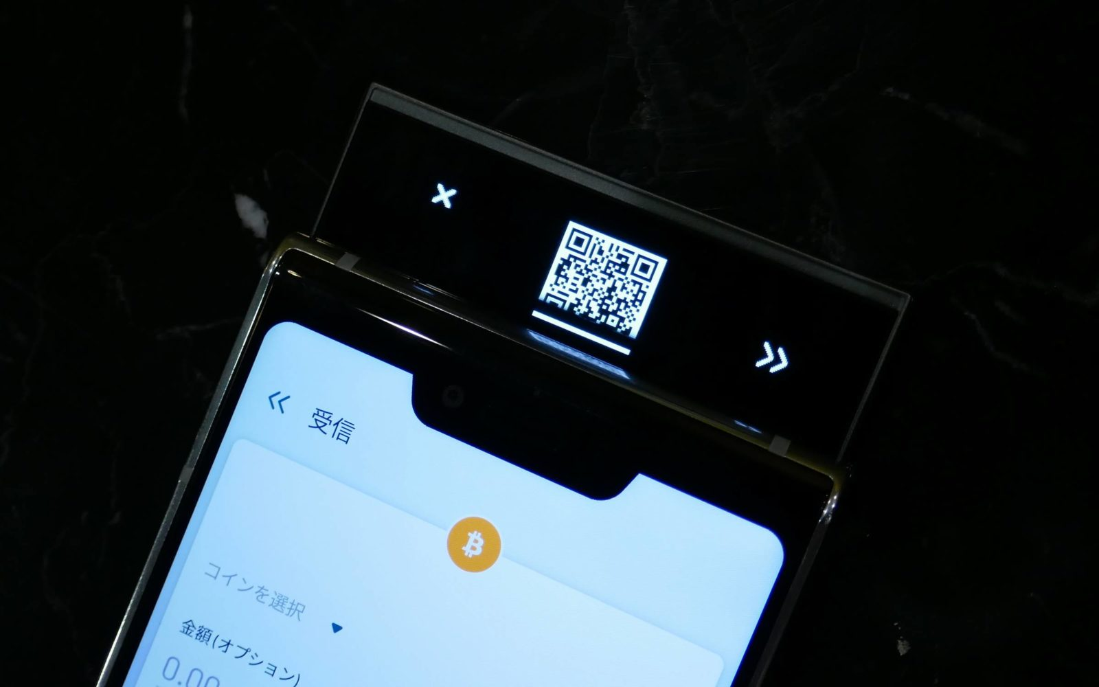 スライド部分の表側には小さなディスプレイがあり、暗号資産にアクセスするためのパスコード入力や受信用のQRコード表示ができる